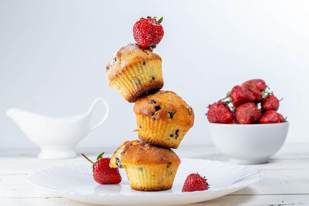 Gestapelte Muffins mit Schokostückchen und frischen Erdbeeren