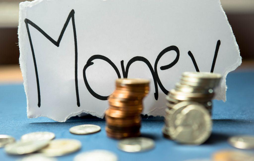 Gestapelte Münzen mit der Schrift Money im Hintergrund