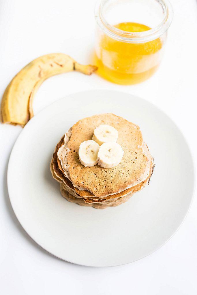 Gestapelte vegane Pfannkuchen mit Banane und Honig auf weißem Hintergrund
