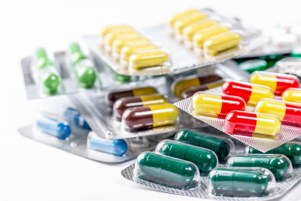 Gestapelte Verpackungen mit verschiedenen Kapseln und Tabletten auf weißem Untergrund