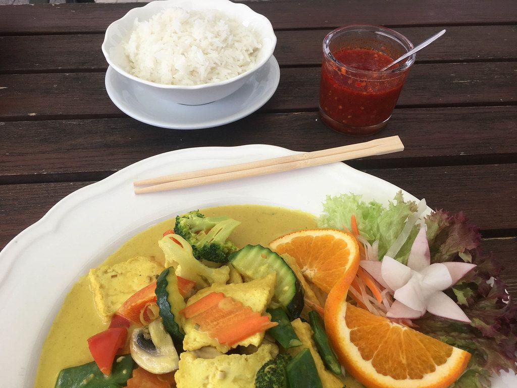 Gesundes Curry-Kurkuma als veganes Mittagessen, mit Reis, scharfer Sauce, Gemüse und Salat, auf einem weißen Teller mit Essstäbchen