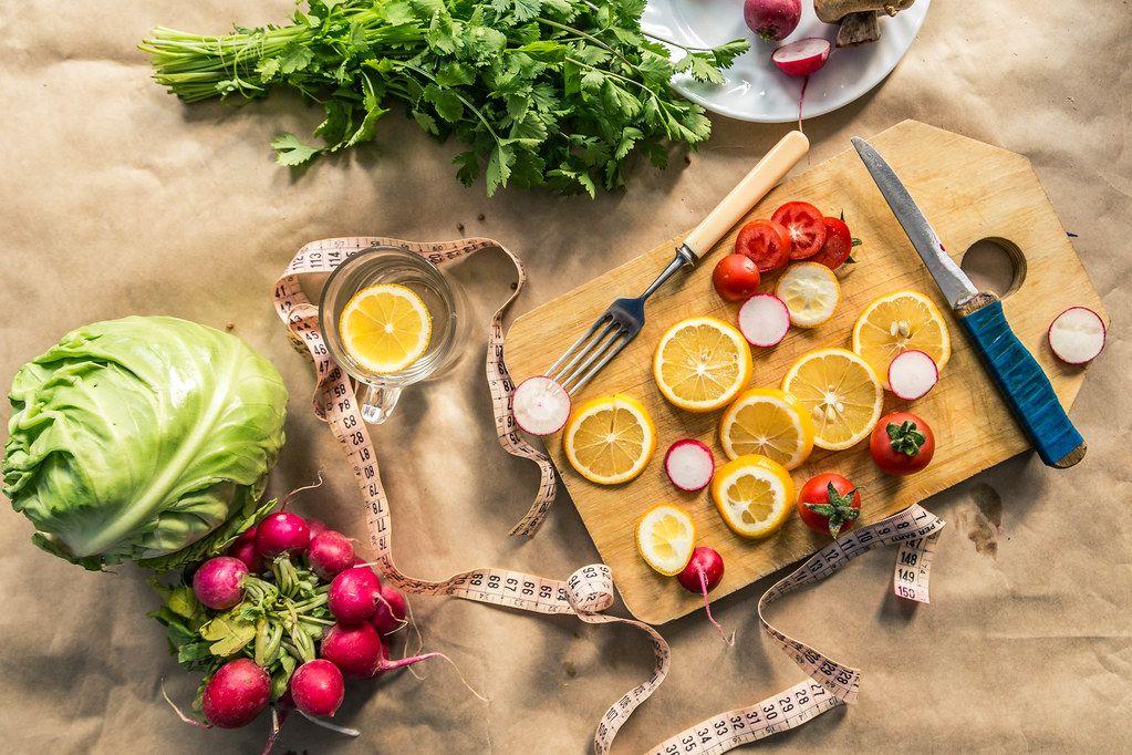 Gesundes,veganes Essen auf dem gesamten Hintergrund ausgebreitet, mit Schneidebrett, Maßband und Zitronenscheiben.