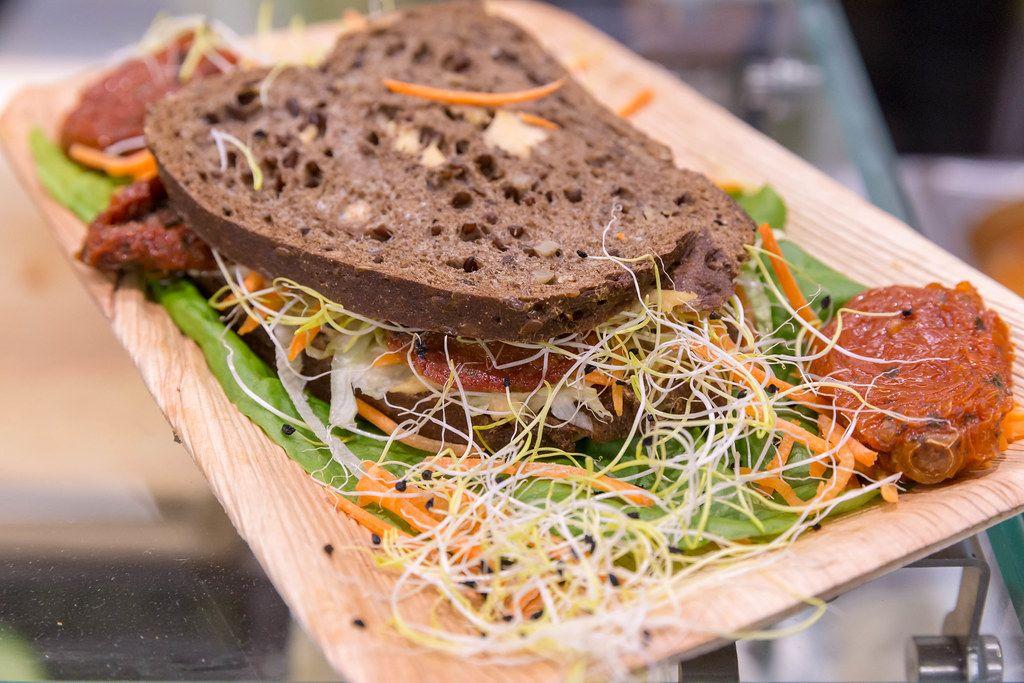 Gesundes vegetarisches Sandwich mit Tomatenpuree, Karotte und verschiedenen Keimen auf Salat-Bett
