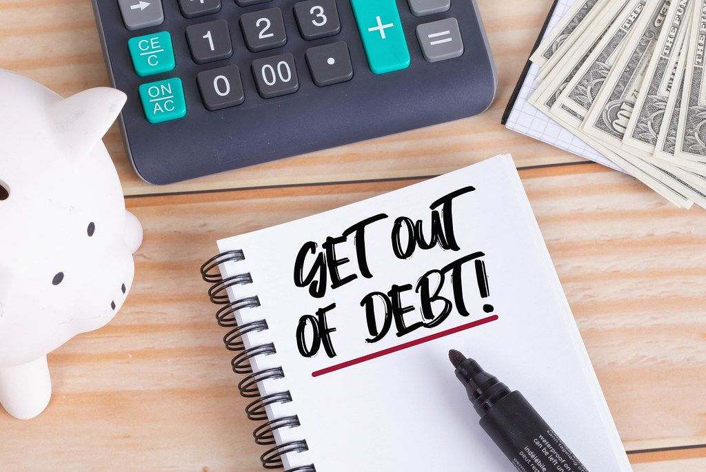 Get out of debt text in notebook with piggy bank and calculator on wooden table