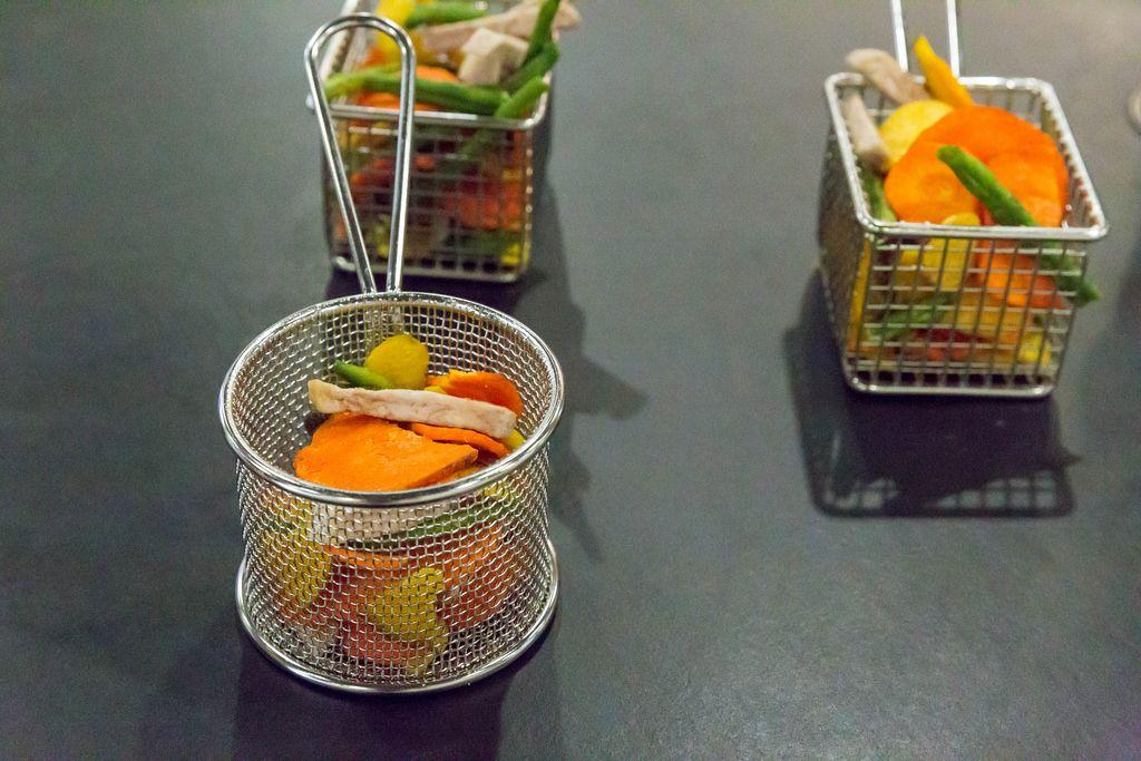 Getrocknetes Gemüse in Friteusenkörben vor schwarzem Hintergrund