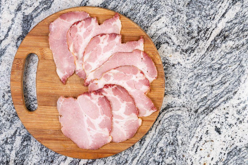 Getrocknetes Schweinefleisch in Scheiben geschnitten auf rundem Holzteller und marmorierter Oberfläche