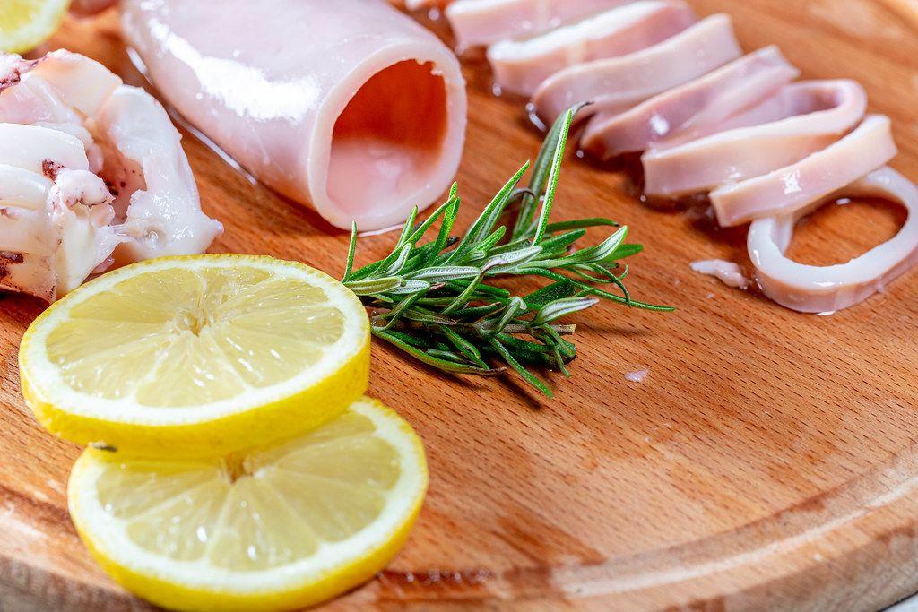 Gewaschener und gekochter Tintenfisch mit Zitronenscheiben und frischem Rosmarin