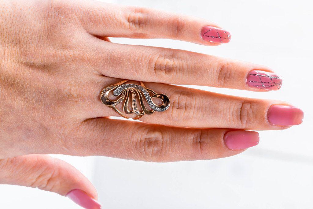 Gewschwungener Ring als Frauenschmuck an der Hand eines Mädchens
