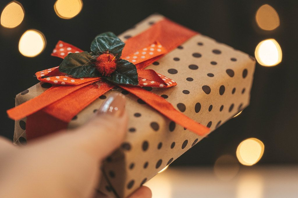 Gift box in hand on bokeh background of glowing garland