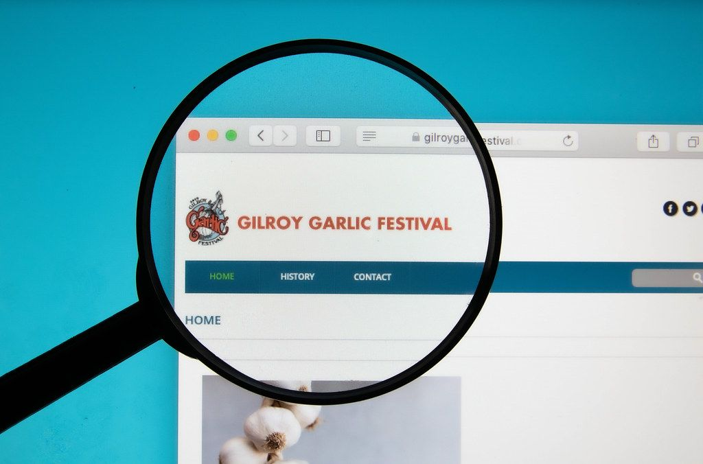 Gilroy Garlic Festival website on a computer screen with a magnifying glass