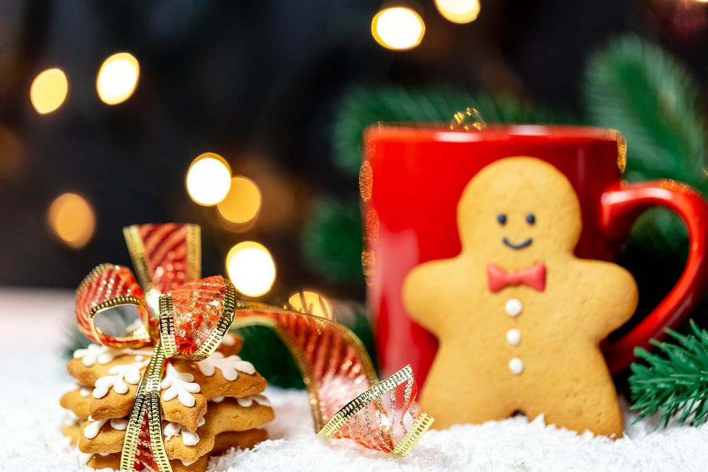 Ginger cookies with a Cup of tea on the background of snow and light garland