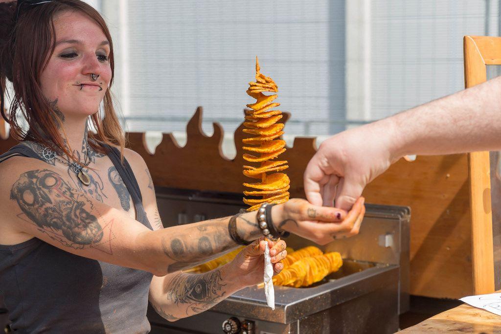 Girl handing out tornado potato to a customer