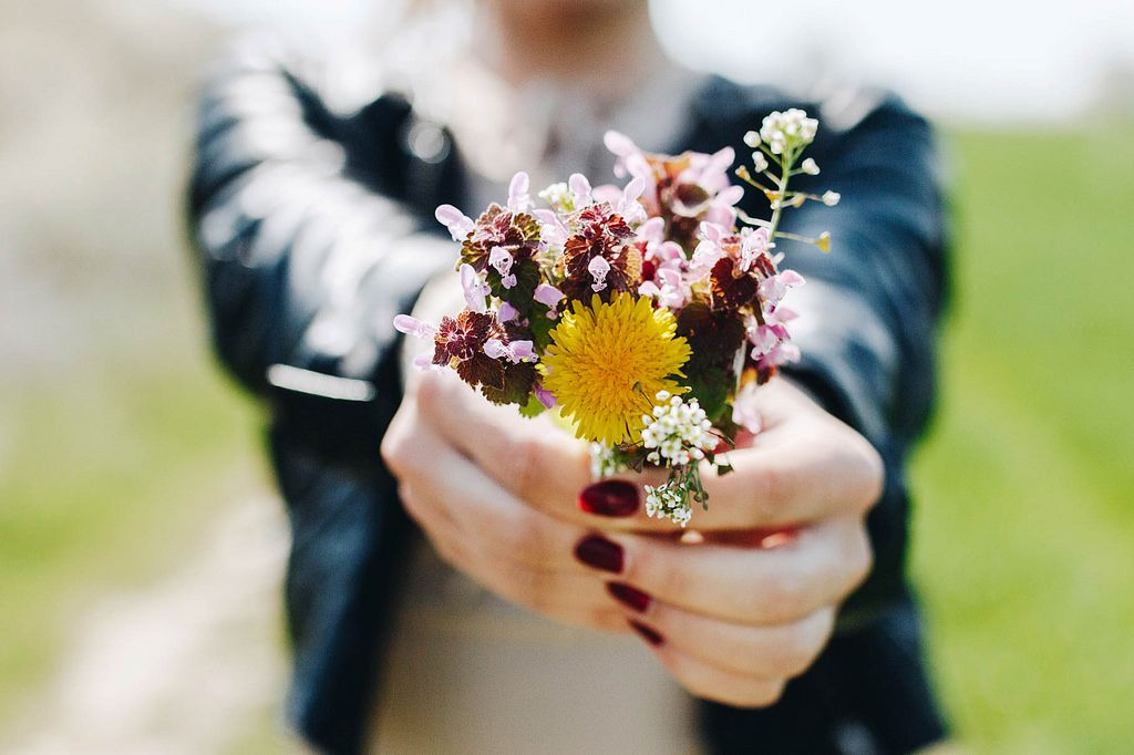 Girl holding wild flowers bouquet . Focused flowers and blurry background