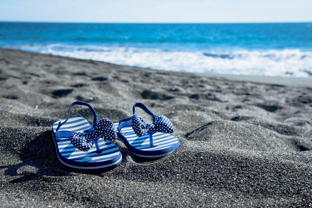 Girl's beach sandals on the sand