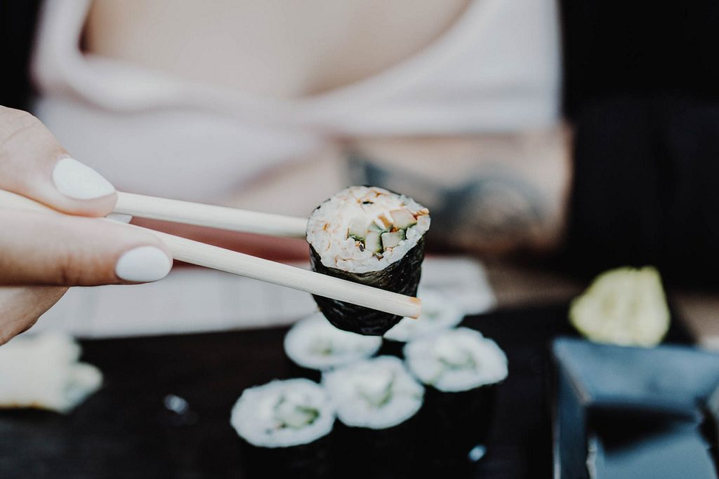 Girl's hand holding sushi with sushi sticks