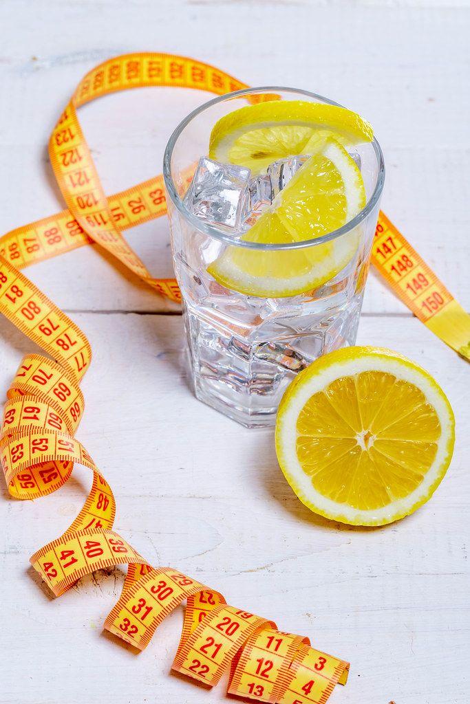 Glas mit kalten Eiswürfeln und Zitrone auf einem weißen Untergrund, umgeben von einem Maßband, als Konzeptbild für ein gesunden Lebensstil