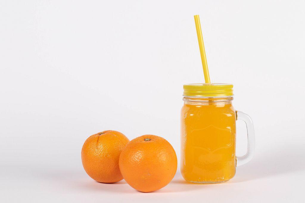 Glas mit Schraubdeckel und Strohhalm gefüllt mit frisch gepresstem Orangensaft neben zwei Orangen