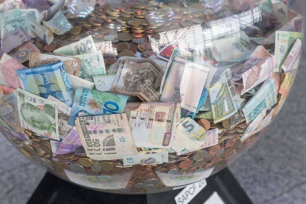 Glasball filled with banknotes and coins of different currencies