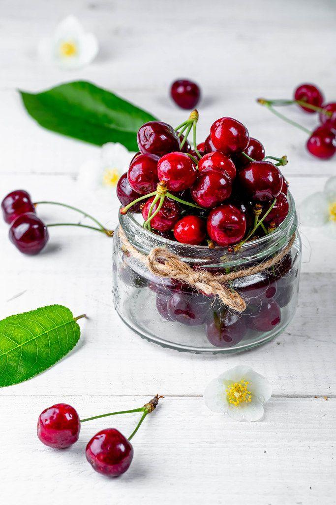 Glasgefäß gefüllt mit frischen Kirschen aus dem Garten, auf einem weißen Holztisch, als gesunder Snack zwischendurch