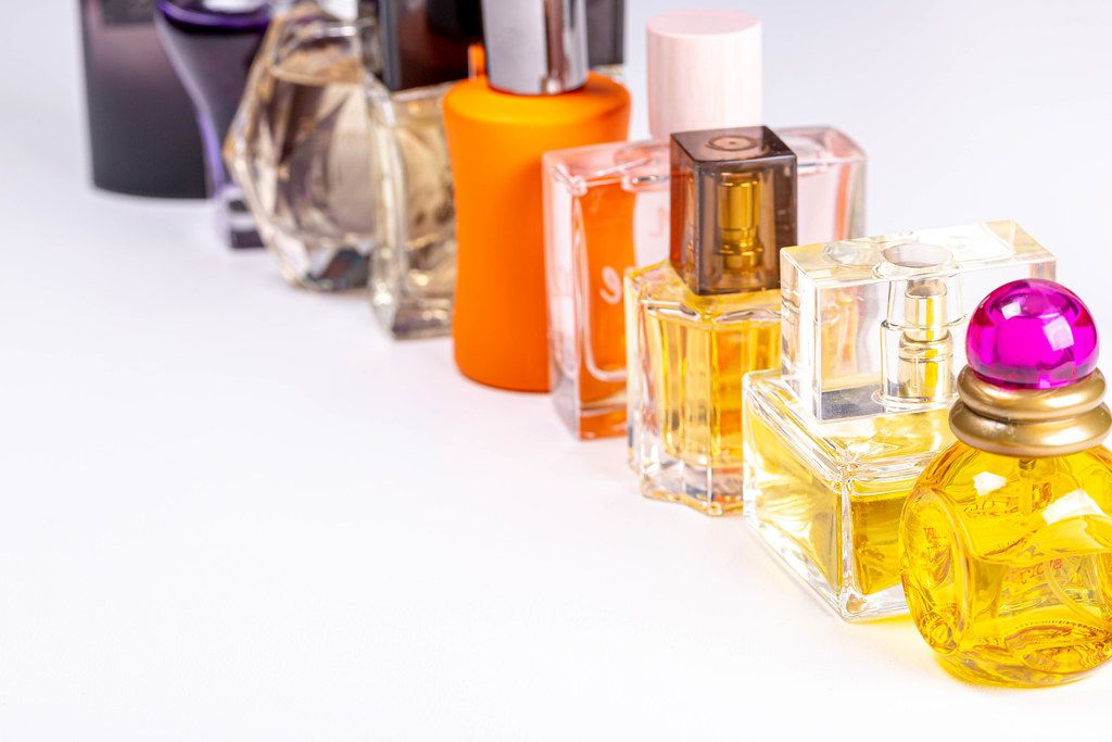 Glass bottles with different perfumes on a white background