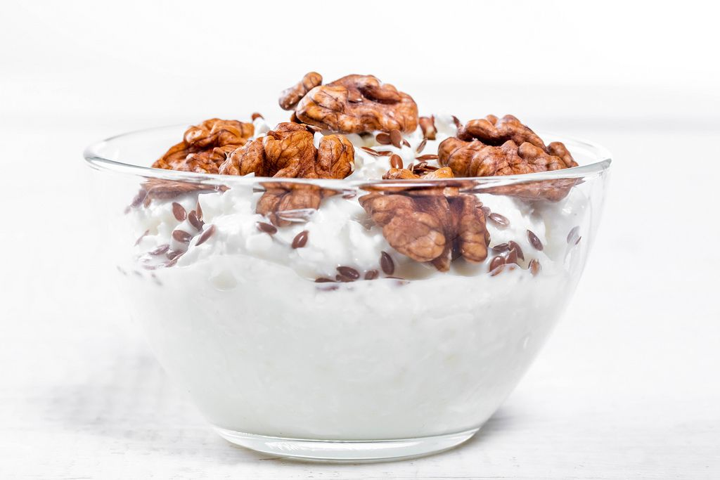 Glass bowl with cottage cheese, nuts and flax seeds on white wooden background