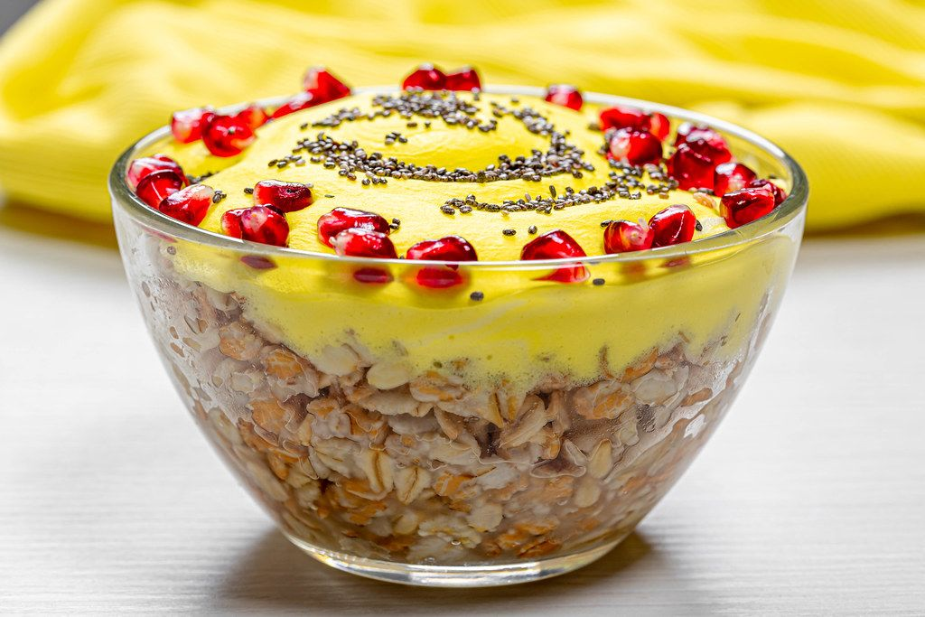 Glass bowl with finished oatmeal with pomegranate and Chia seeds