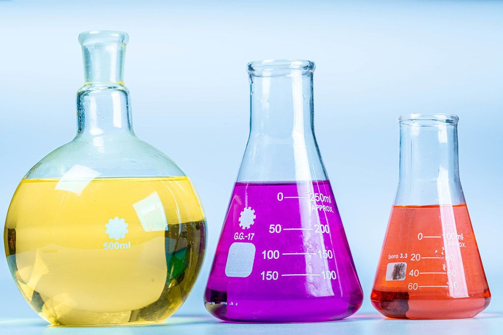 Glass flasks of different shapes with colored solutions. Concept of chemical experiments