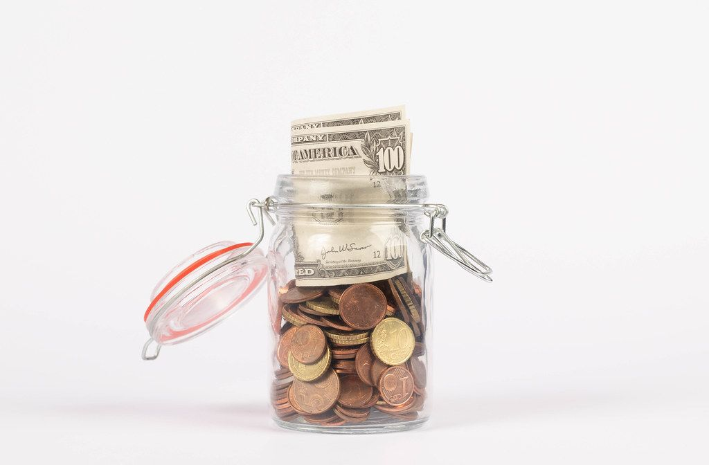 Glass jar for money on white background