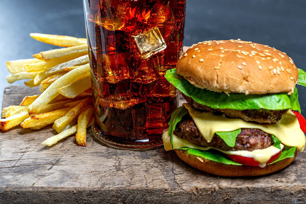 Glass of Cola with ice, French fries and Burger close-up