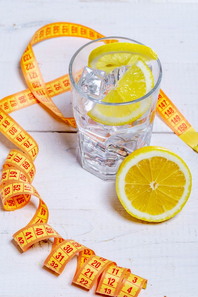 Glass of cold water with ice cubes and lemon on white wooden background with measuring tape-healthy lifestyle concept