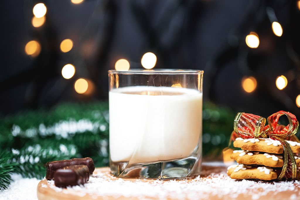Glass of milk with ginger cookies on Christmas background