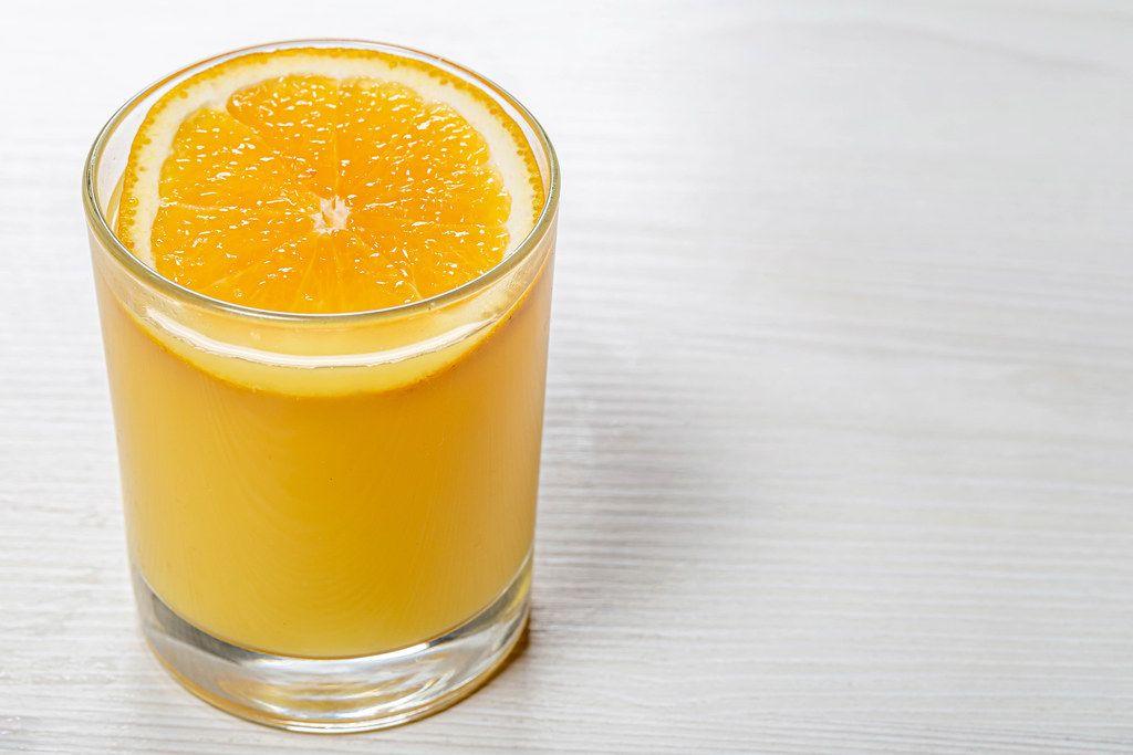 Glass of orange juice with a slice of orange on white wooden background (Flip 2019)