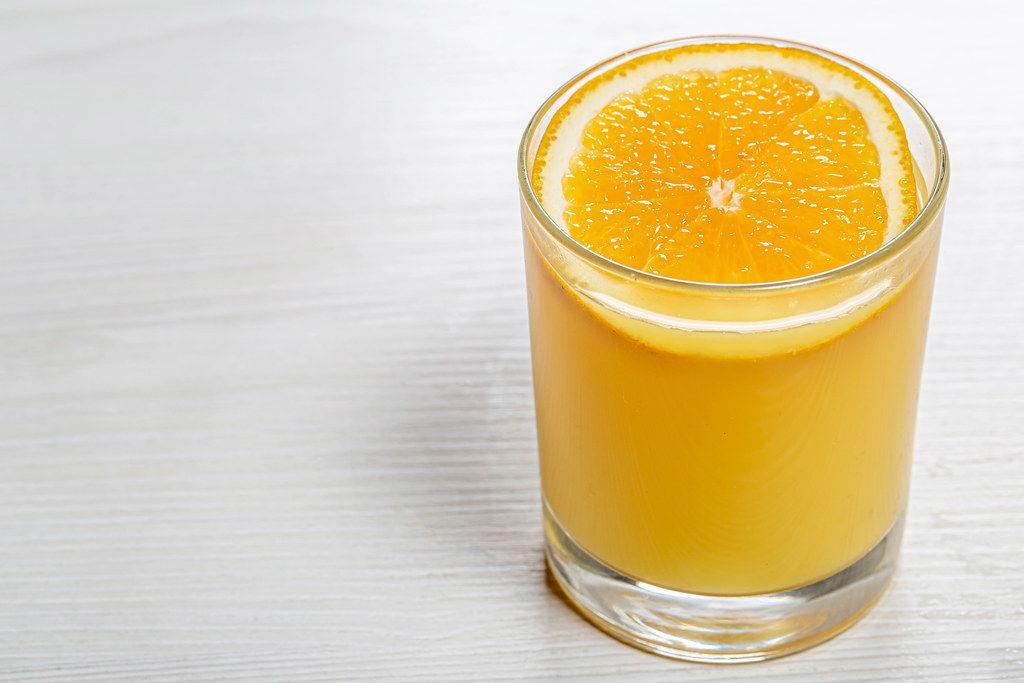 Glass of orange juice with a slice of orange on white wooden background
