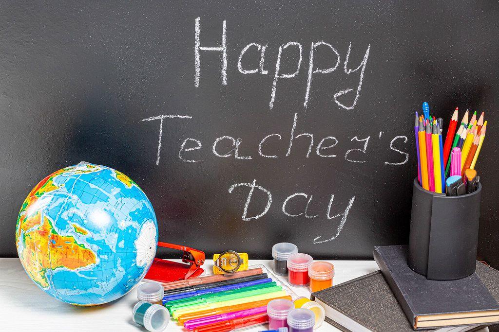 Globe and school supplies with teg Happy Teacher's Day on blackboard