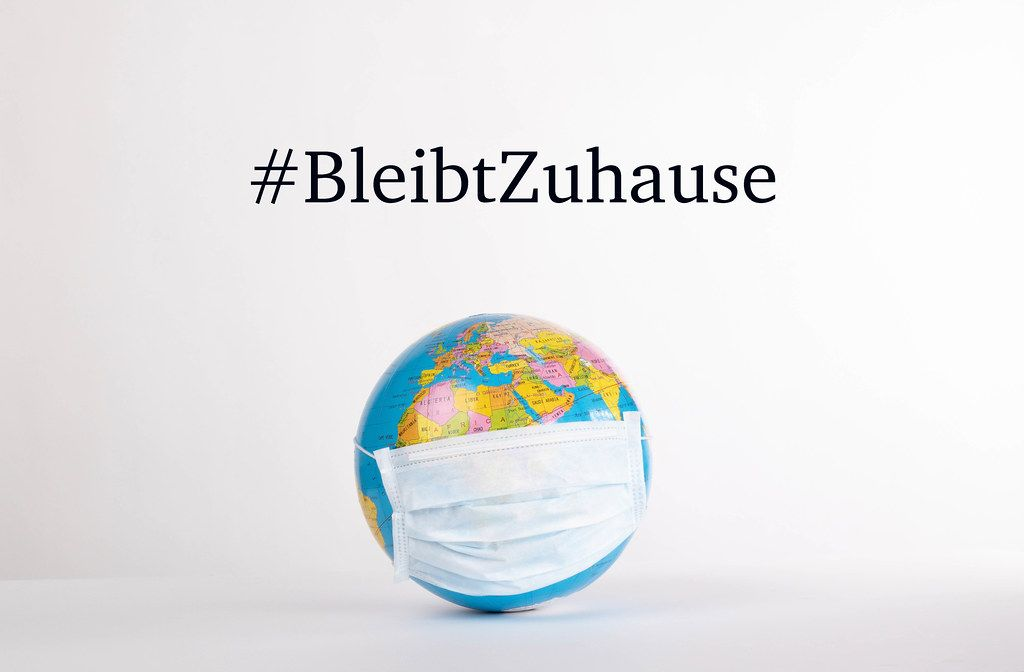 Globe with medical mask and #BleibtZuhause text on white background