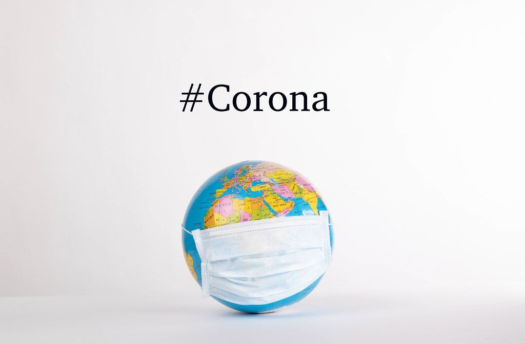 Globe with medical mask and #Corona text on white background.jpg