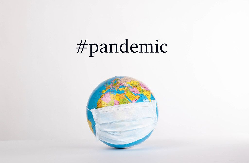 Globe with medical mask and #pandemic text on white background