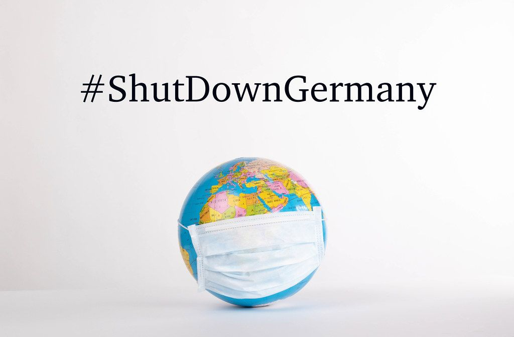 Globe with medical mask and #ShutDownGermany text on white background