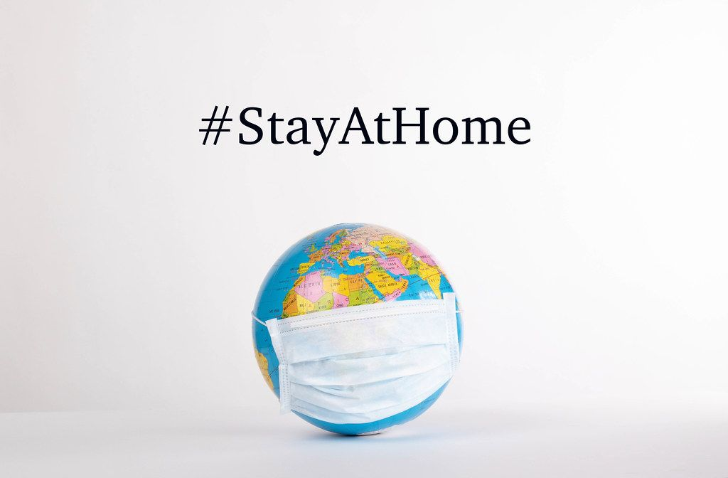 Globe with medical mask and #StayAtHome text on white background