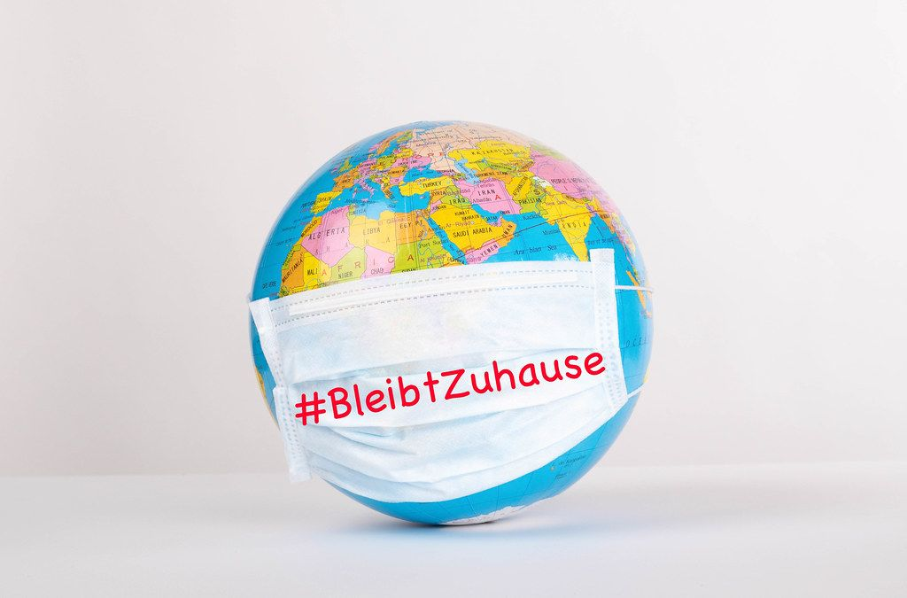 Globe with medical mask on white background and #BleibtZuhause text