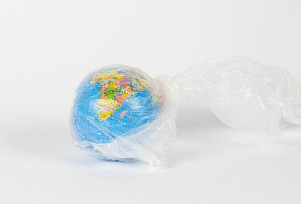 Globus in einer Plastiktüte auf weißem Hintergrund - Konzept zum Plastikproblem