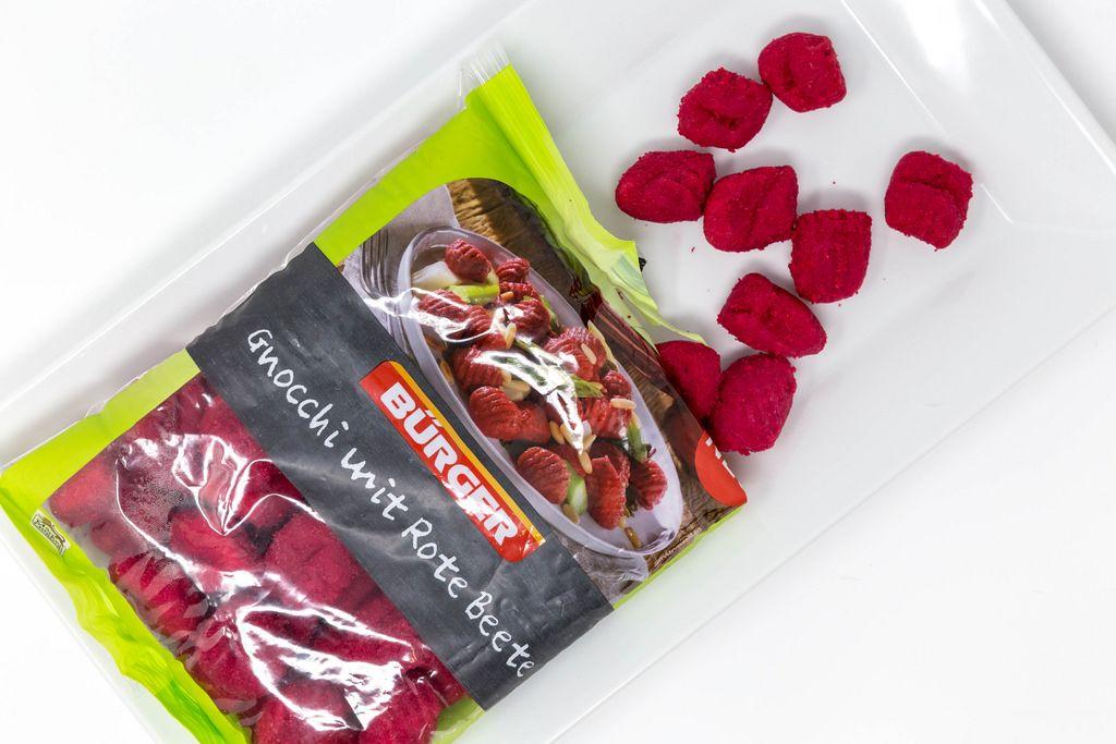 Gnocchi mit roter Bete fallen aus der Verpackung auf einen Teller