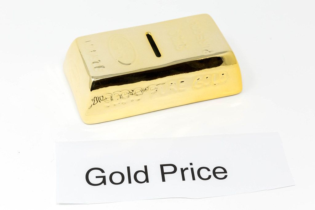 Gold bars and paper with the words GOLD PRICE in front of white background