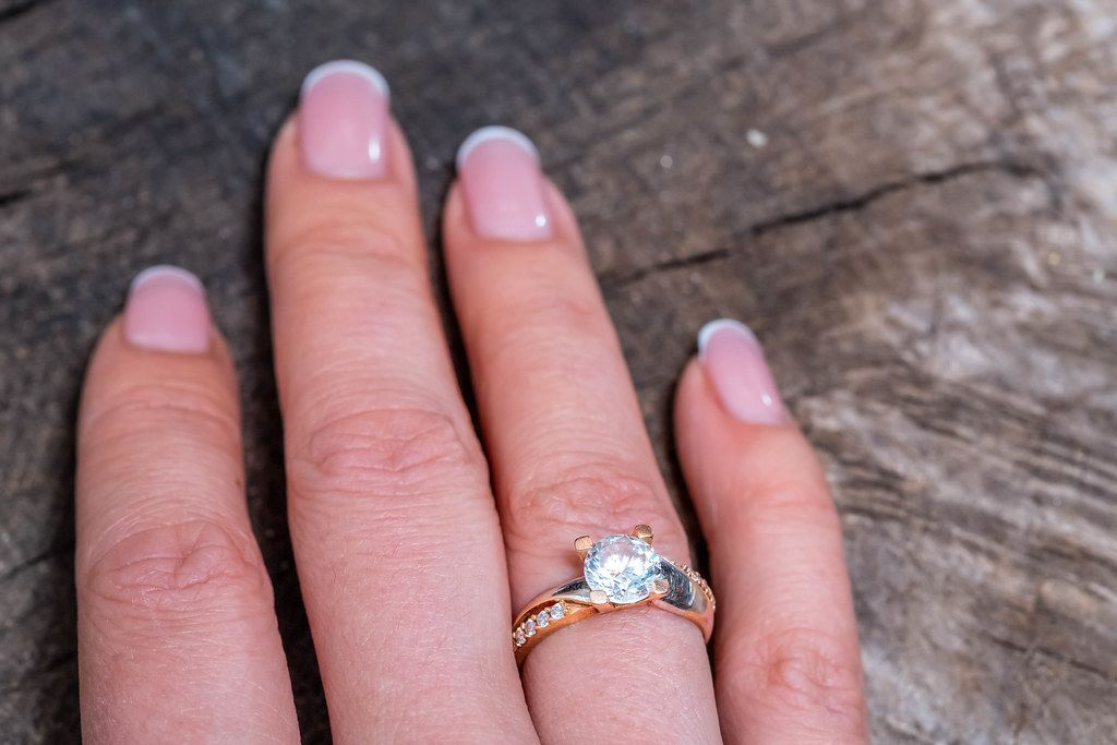 Gold ring on woman's finger on old wooden background