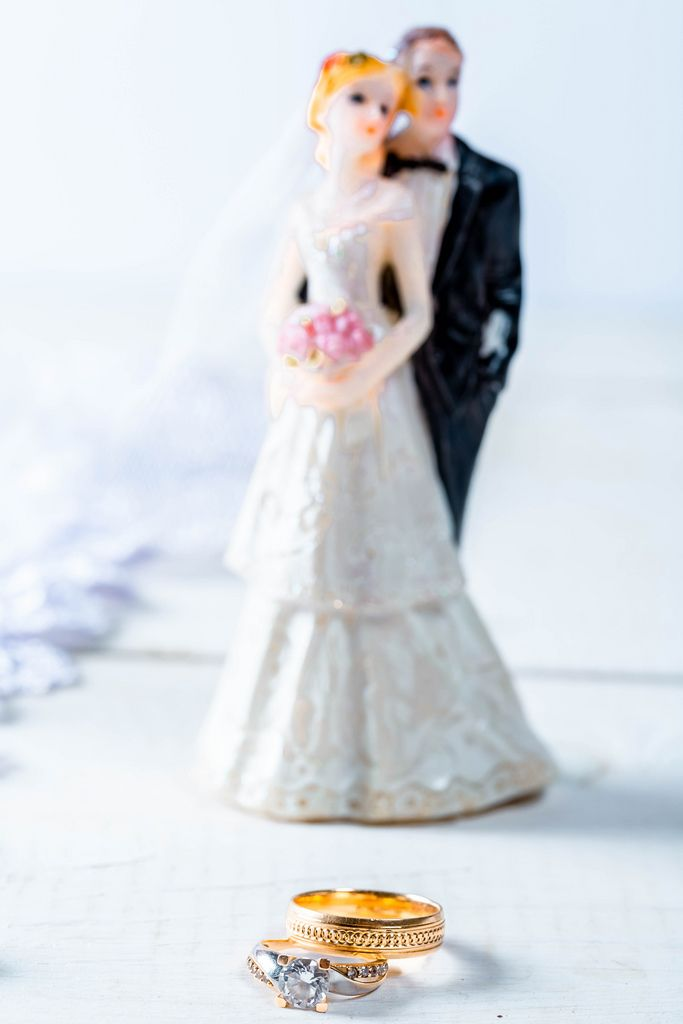 Gold wedding rings, behind the figure of the bride and groom
