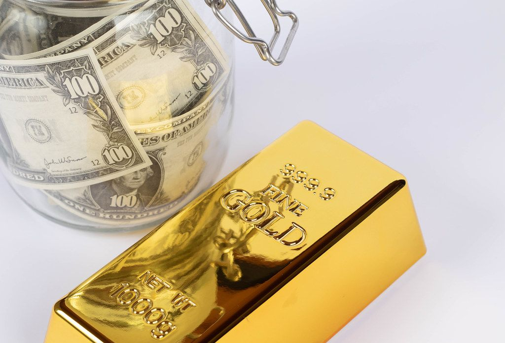 Goldbarren mit einem Glasgefäß, das mit Geld gefüllt ist