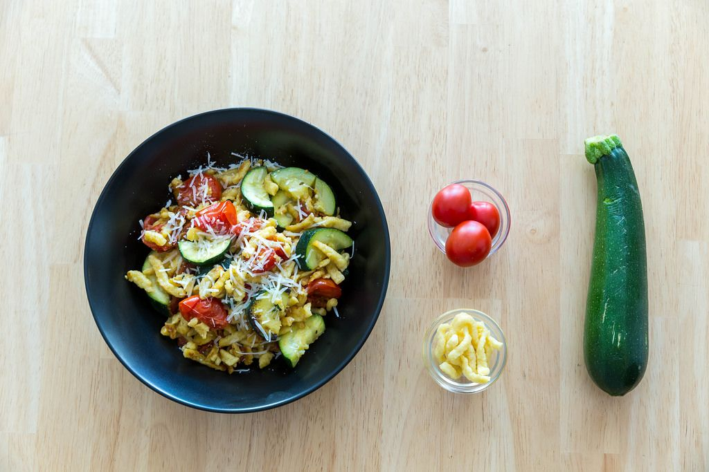 Goldbraun gebratene Spätzle mit getrockneten Tomaten und Zucchini inklusive Zutaten. Draufsicht