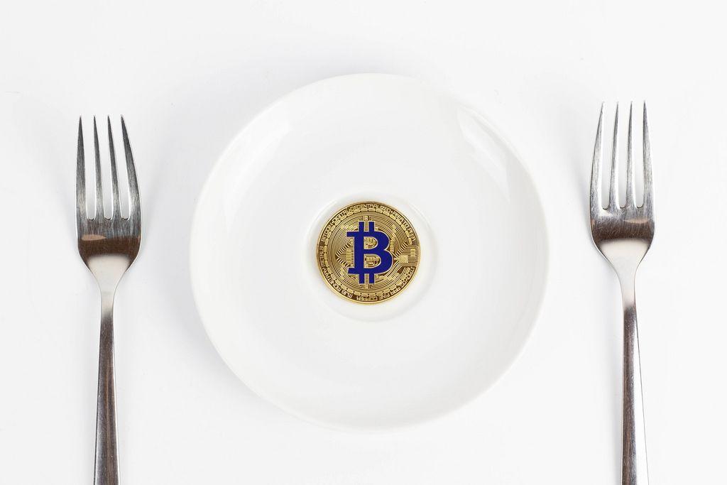 Golden Bitcoin coin on white dish