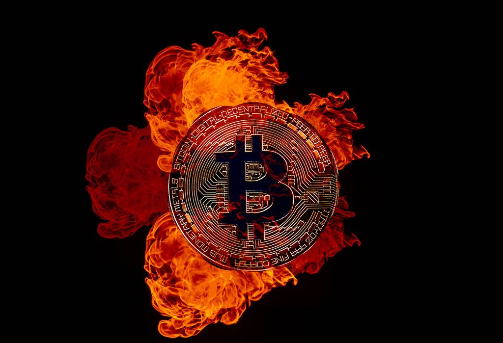 Golden Bitcoin on fire over black background