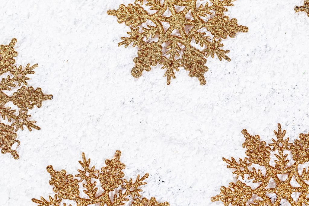 Golden snowflakes on snow background. Winter holidays concept